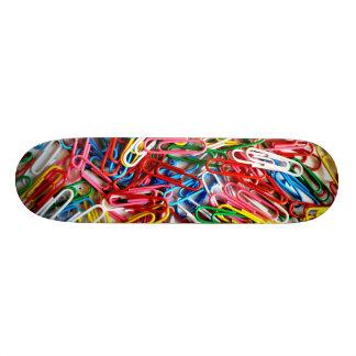 Clips de papel coloridos en el fondo blanco tabla de skate