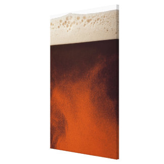 Close up image of amber colored beer with frothy canvas print