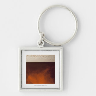 Close up image of amber colored beer with frothy key chains
