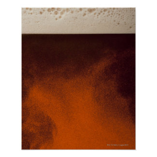 Close up image of amber colored beer with frothy poster