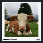 """Close up of a brown and white cow laying down wall decal<br><div class=""""desc"""">Close up of a brown and white cow laying down in a field. 2 other cows are in the background. In the background is hills and pine trees.</div>"""