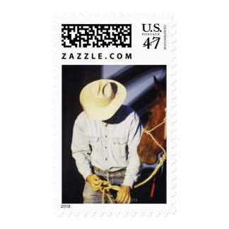 Close-up of a cowboy tying a rein postage stamp