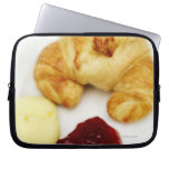 Close-up of a croissant served with butter and computer sleeve