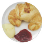 Close-up of a croissant served with butter and plate