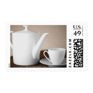 Close-up of a cup and a saucer with a tea kettle stamps