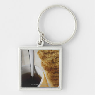 Close-up of a cup of coffee with cookies keychain