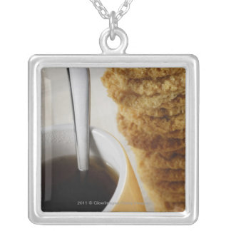 Close-up of a cup of coffee with cookies silver plated necklace