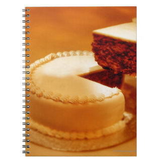 close-up of a cut piece of cake being taken out notebook