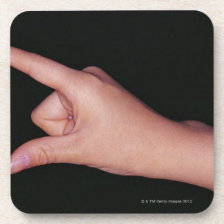 Close-up of a hand with finger and thumb beverage coasters