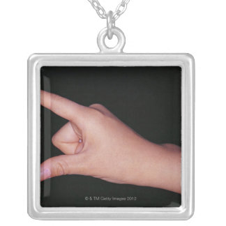 Close-up of a hand with finger and thumb square pendant necklace