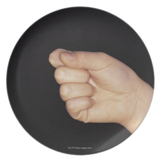 Close-up of a hand with fist clenched melamine plate