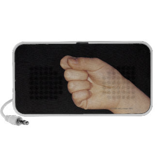 Close-up of a hand with fist clenched mp3 speaker