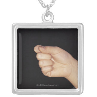 Close-up of a hand with fist clenched square pendant necklace