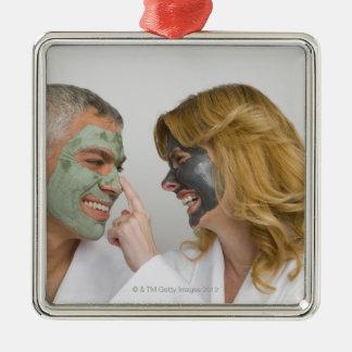 Close-up of a mature couple wearing facial masks metal ornament