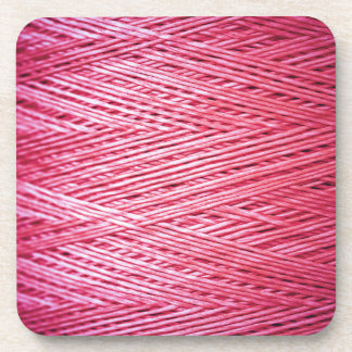 Close up of a spool of synthetic pink thread beverage coaster