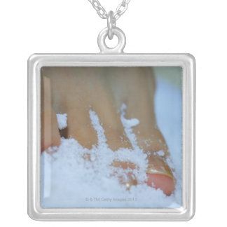 Close-up of a woman's foot in salt silver plated necklace
