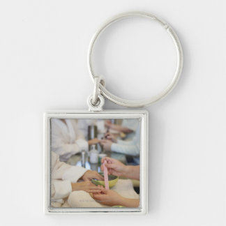 Close-up of a woman's hand getting a manicure keychain