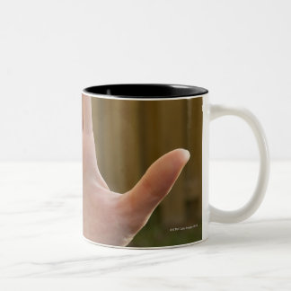 Close-up of a woman's hand making a hand sign Two-Tone coffee mug