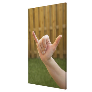 Close-up of a woman's hand making a shaka sign canvas print