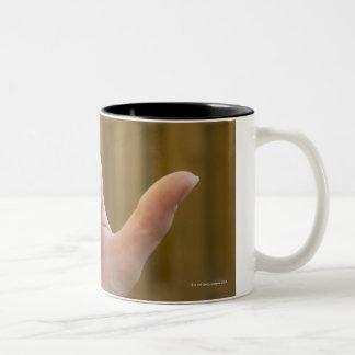 Close-up of a woman's hand making a shaka sign Two-Tone coffee mug