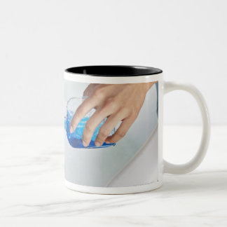 Close-up of a woman's hand pouring aromatherapy Two-Tone coffee mug