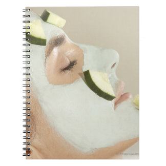 Close-up of a young woman wearing a facial mask notebook