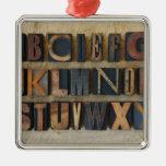 Close up of alphabet on letterpress square metal christmas ornament