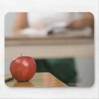 Close-up of an apple on a desk mouse pad