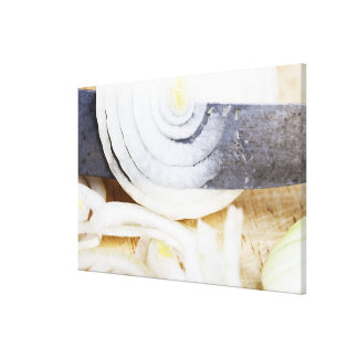 close-up of an onion, being cut into slices canvas print