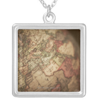 Close-up of antique globe 3 silver plated necklace