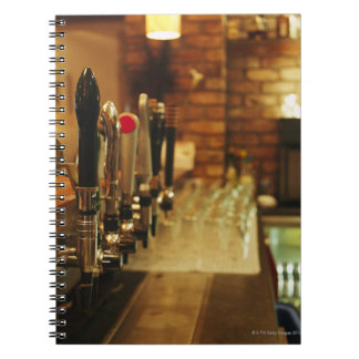 Close-up of beer taps in bar 2 spiral notebooks