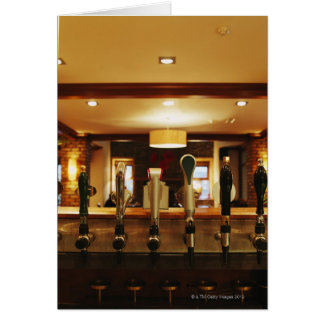 Close-up of beer taps in bar card