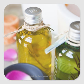 Close up of bottles with massage oils square sticker