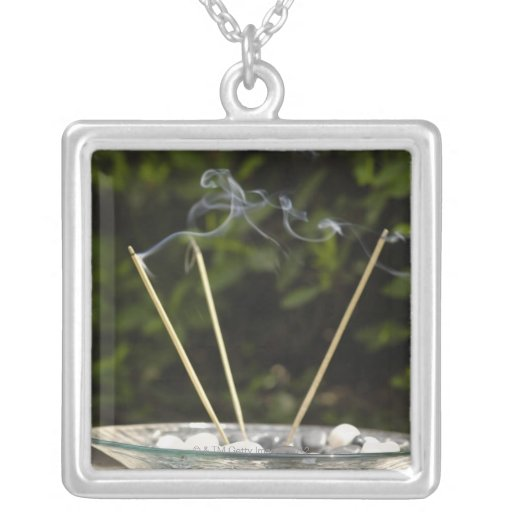 Close-up of burning incense sticks with pebbles custom jewelry
