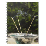 Close-up of burning incense sticks with pebbles spiral note books