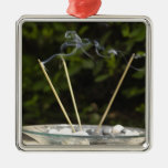 Close-up of burning incense sticks with pebbles christmas tree ornament
