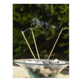 Close-up of burning incense sticks with pebbles postcard