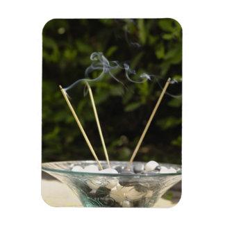 Close-up of burning incense sticks with pebbles rectangular photo magnet