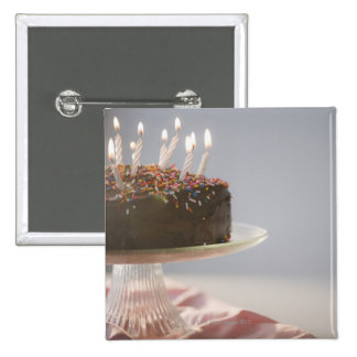 Close up of chocolate birthday cake with candles 2 inch square button