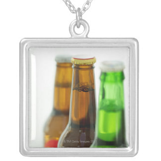 close-up of colored bottles of beer silver plated necklace