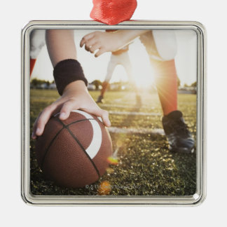 Close up of football center preparing to snap metal ornament