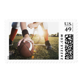 Close up of football center preparing to snap postage
