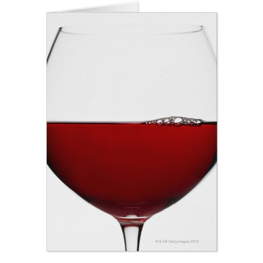 Close up of glass of red wine on white card