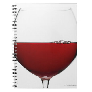 Close up of glass of red wine on white notebook