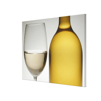 Close up of glass of white wine and wine bottle canvas print