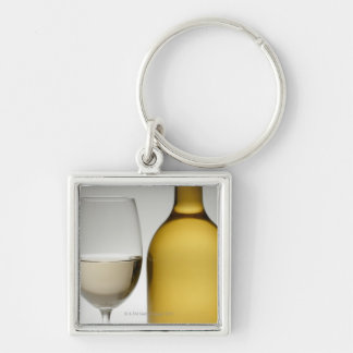 Close up of glass of white wine and wine bottle keychain