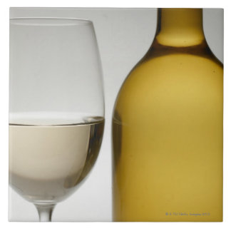 Close up of glass of white wine and wine bottle large square tile