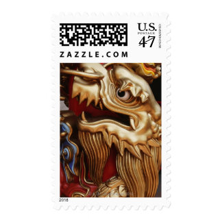 Close up of gold dragon on temple pillar postage stamp