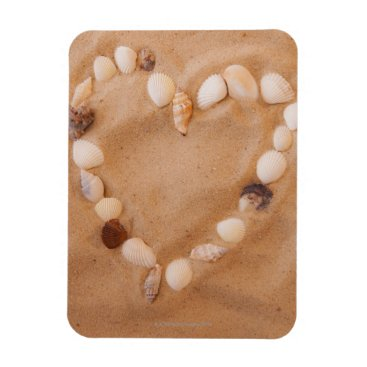 Valentines Themed Close up of heart shape made of shells on sand magnet