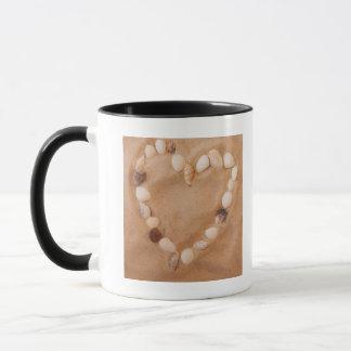 Close up of heart shape made of shells on sand mug